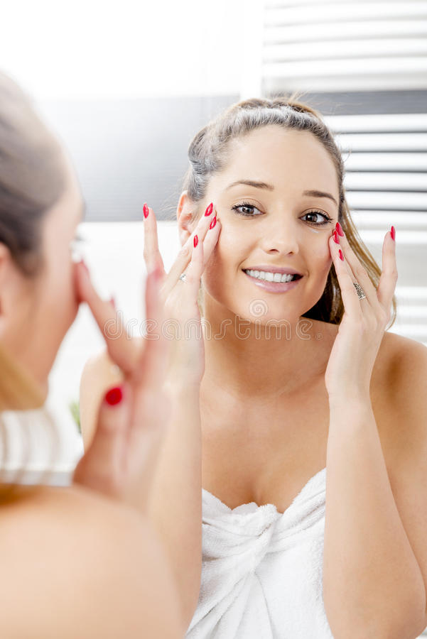Attractive girl putting anti-aging cream stock images