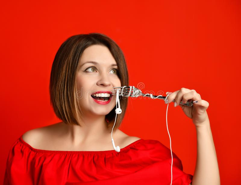 Attractive girl in red dress holding a fork in hands. on the headphone plug. prepared to eat. royalty free stock image
