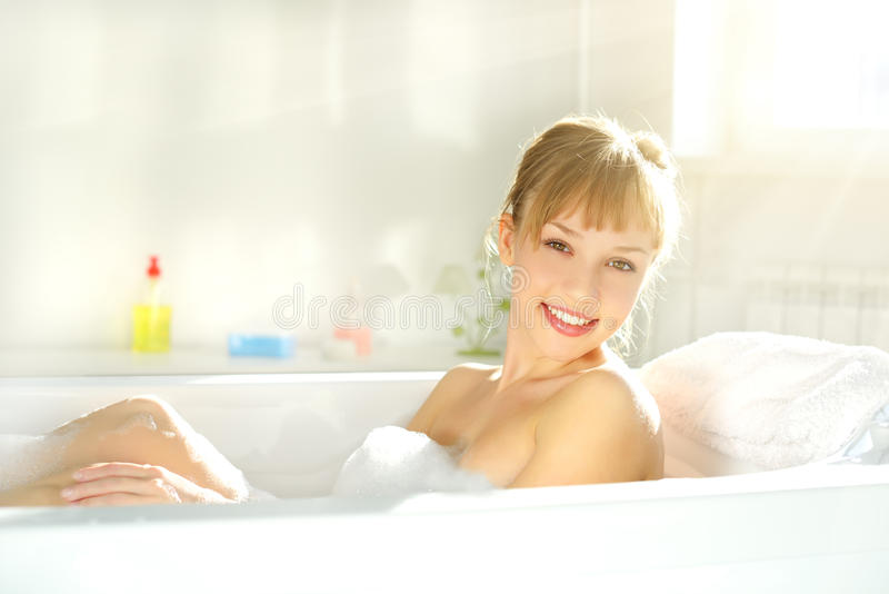 Attractive girl relaxing in bath. On light background royalty free stock images