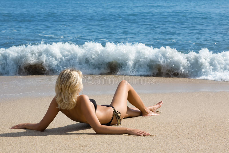 Attractive girl relaxing on the beach by the sea. Sunny day stock photography