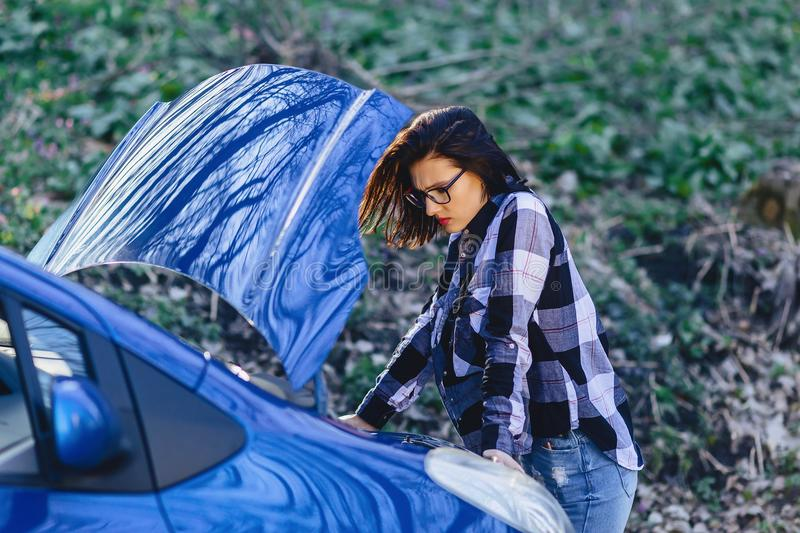 attractive girl repairs car on road royalty free stock photos