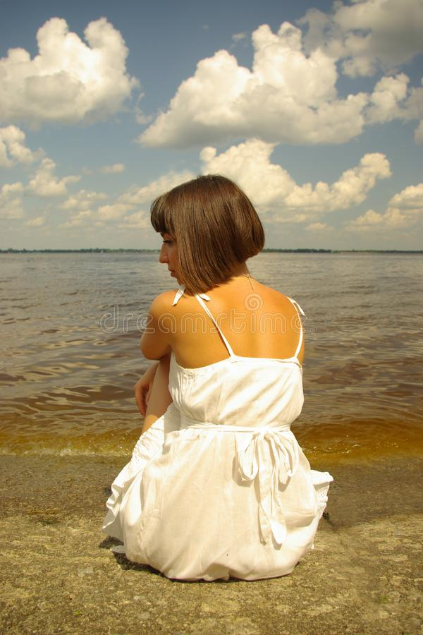 Attractive girl sitting alone royalty free stock photography