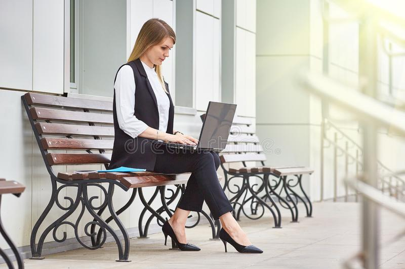 Attractive girl sitting on a bench near a business building with a laptop. royalty free stock images