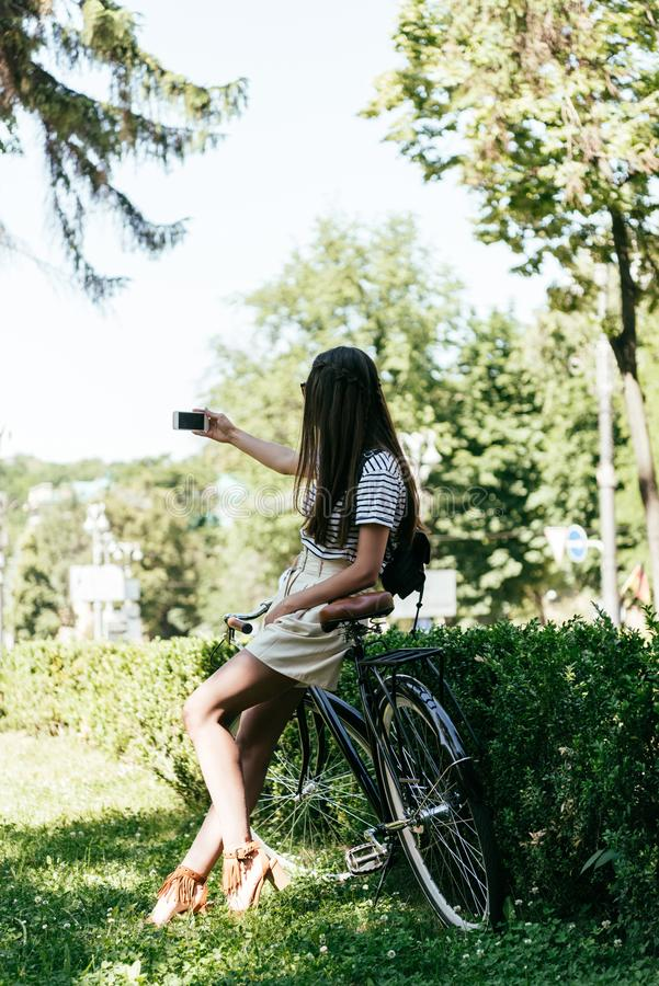 attractive girl sitting on bicycle and taking selfie with smartphone on street royalty free stock photography