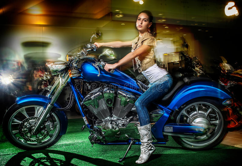 Attractive girl sitting on a blue motorcycle, moto show stock photo