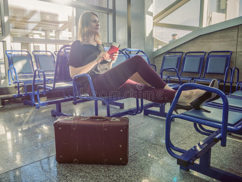 Attractive girl sitting in the hall, waiting for the flight. Dreams of vacation. The journey with retro vintage suitcase. royalty free stock photography