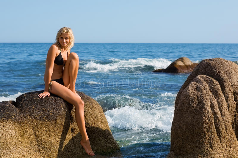 Attractive girl is sitting on a rock. By the sea stock image
