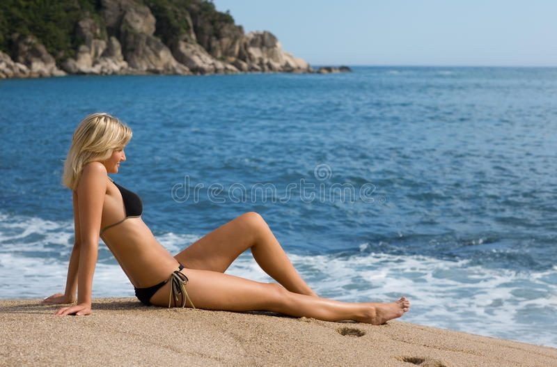 Attractive girl sitting on the sand beside the sea. Sunny day stock image
