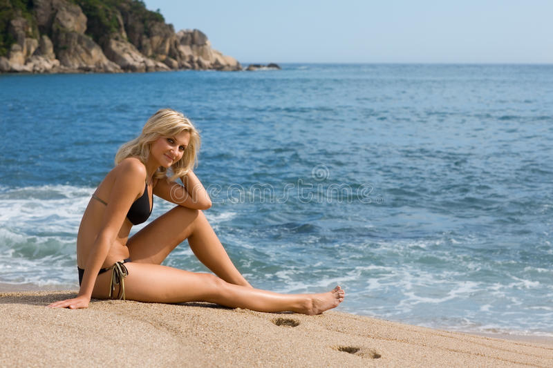 Attractive girl sitting on the sand beside the sea. Sunny day stock photo