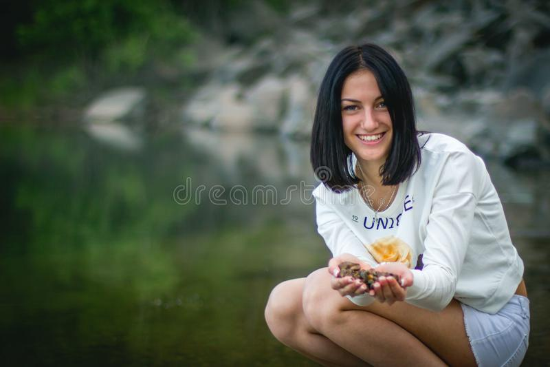 Attractive girl in sports clothes smiling and shows in the hands of stones from the river royalty free stock images