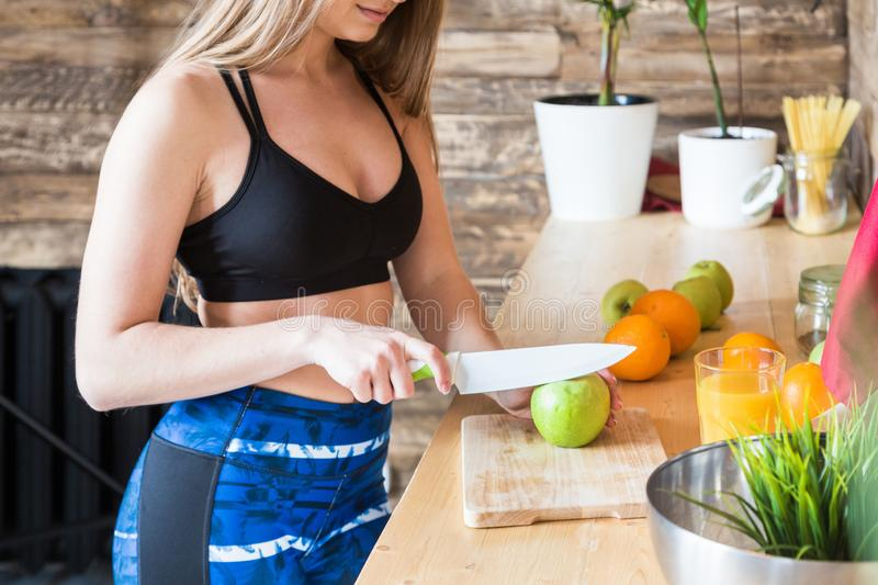 Attractive girl in sportswear preparing a healthy breakfast in the kitchen before training, cutting fruit and making. Fresh juice. Healthy lifestyle, fitness stock photography