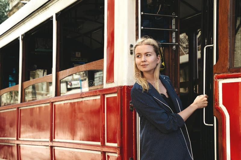 Attractive girl standing in the doorway of red retro tram on the street. Popular sight of Istanbul, Turkey. District royalty free stock photo