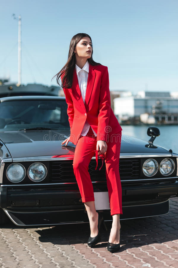 Attractive girl standing next to a retro sport car on the sun. Fashion woman in a red suit and sunglasses waiting near classic car royalty free stock photography