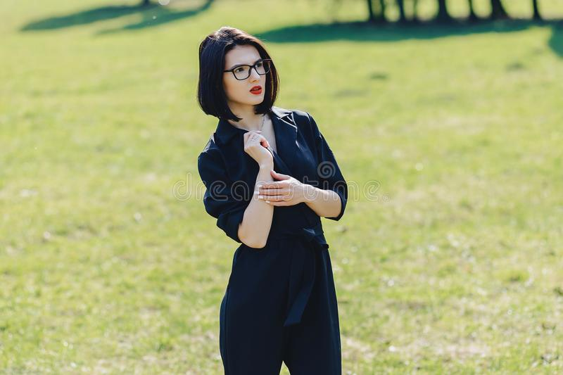 attractive girl in suit on green grass background stock photography