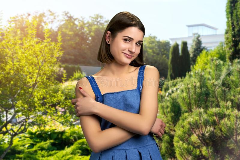 Attractive girl on summer nature background. Coquette young woman with brown short hair smiling and looking at camera outdoor stock image