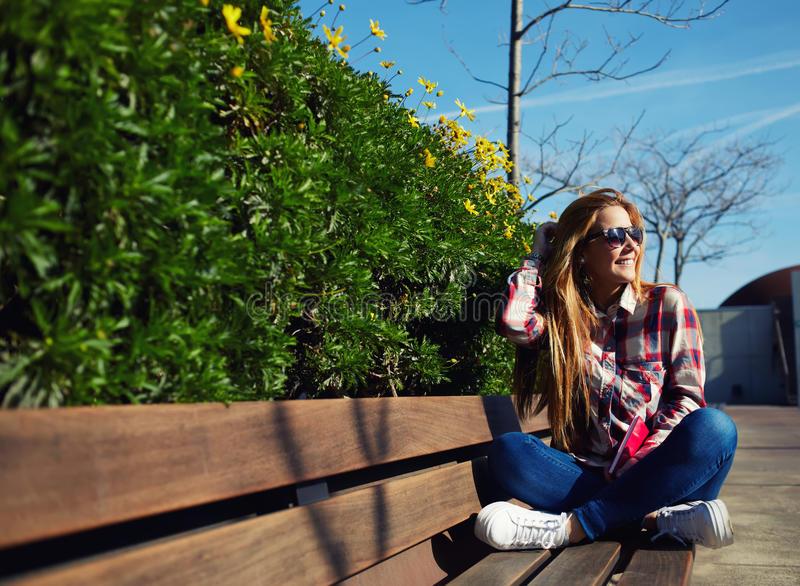 Attractive girl in sunglasses relaxing in the spring park while read book. Charming blonde hair young woman enjoying the sun at beautiful day outdoors stock images