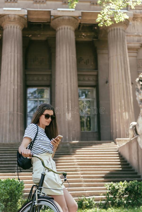 attractive girl in sunglasses sitting on bike and using smartphone near beautiful building with columns royalty free stock image