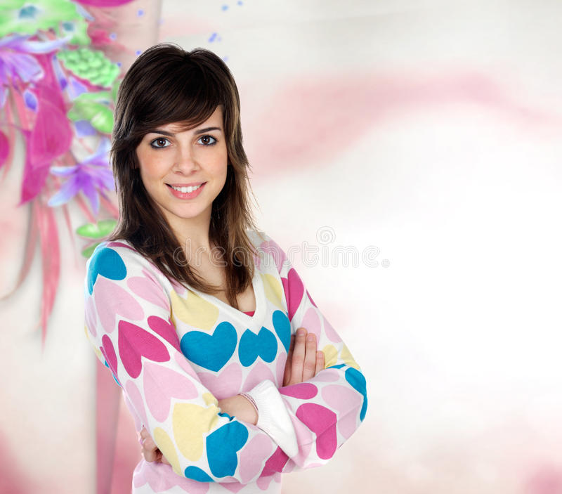 Attractive girl with sweater heart. Attractive young casual girl with a pink and flowered background stock photo