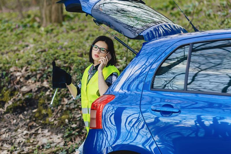 attractive girl talking by phone near car on road in safety jack royalty free stock images