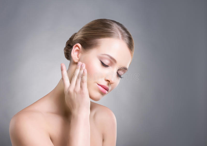 Attractive girl touching her smooth skin over cheeks on grey background.  royalty free stock photography