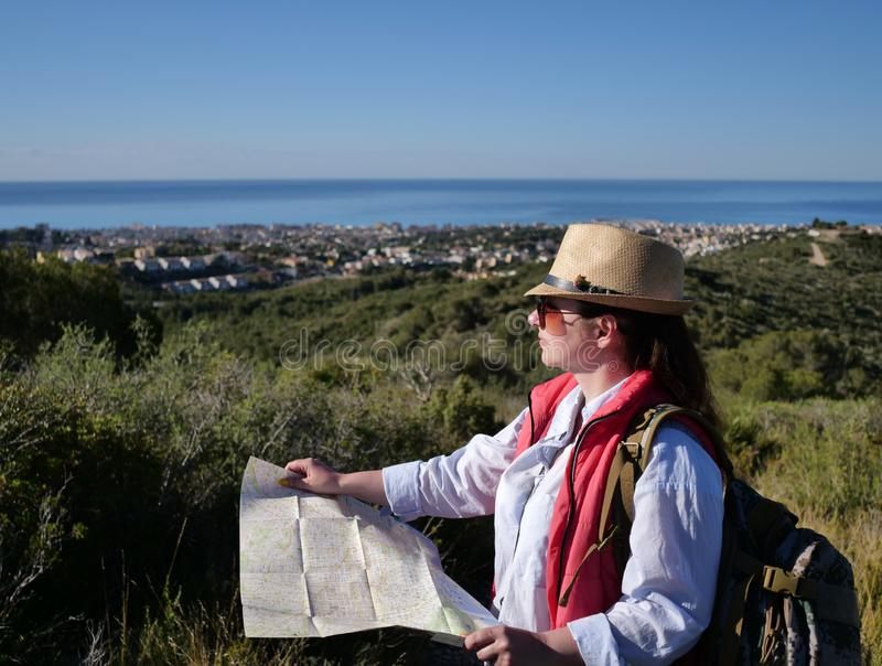 Attractive girl tourist in a hat and sunglasses with a map of the area looks at the city under the hill stock image