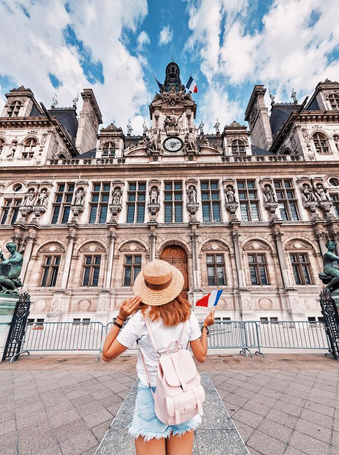Girl traveler with a cute backpack enjoys the view of the stunning Gothic architecture of the old town Hall in Paris. stock photography