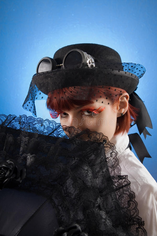 Attractive girl in Victorian style clothes. With umbrella, studio shot over blue background royalty free stock photos