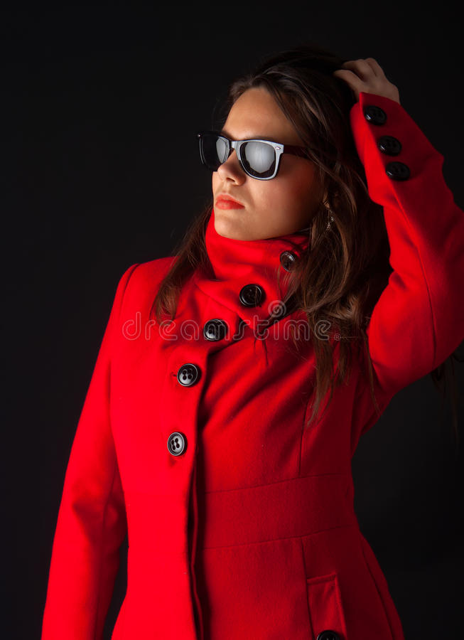 Attractive girl wearing sunglasses and winter coat stock photography