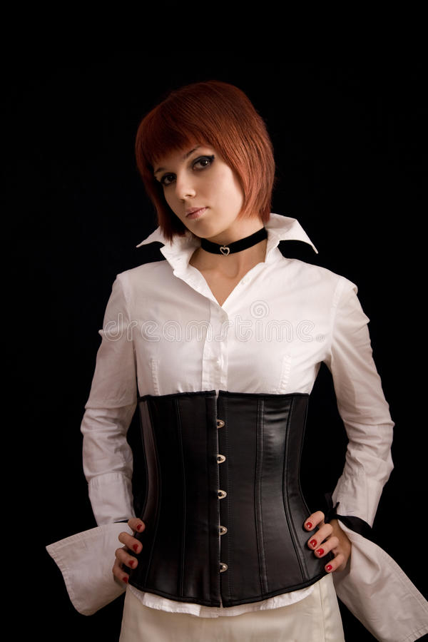 Attractive girl in white blouse and leather corset. Isolated on black background royalty free stock images