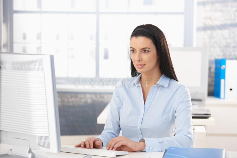 Attractive girl working in office. Attractive girl working on desktop computer in office, looking at screen, smiling royalty free stock photo