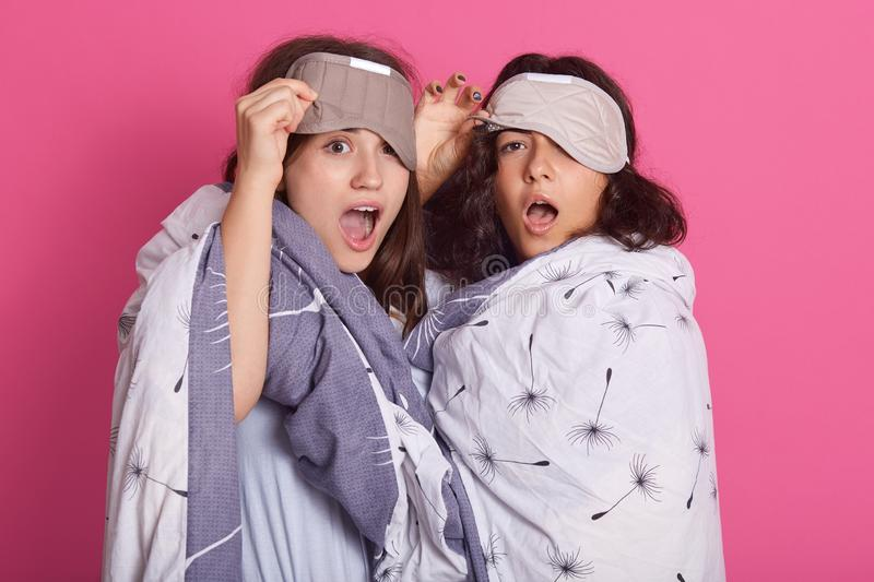Attractive girls having pajama party, standing wearing blanket and blindfolds, having astonished facial expressions, posing with. Open mouths. Studio shot of royalty free stock photos