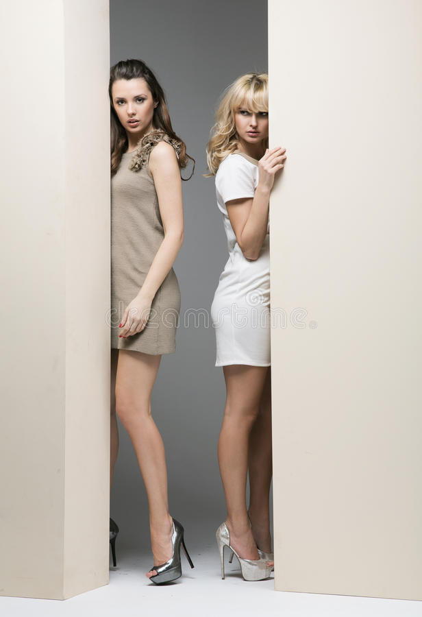 Attractive women hiding theirselves behind the wall royalty free stock photo