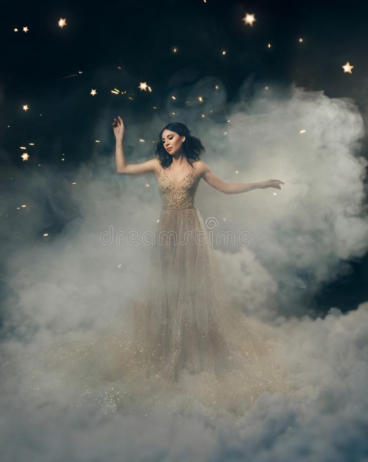 An attractive goddess stands in the clouds in a luxurious, gold, sparkling dress. Whimsical hairstyle. Against the royalty free stock image