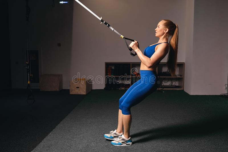 Attractive good looking fitness girl developing muscles in the sport club stock photos