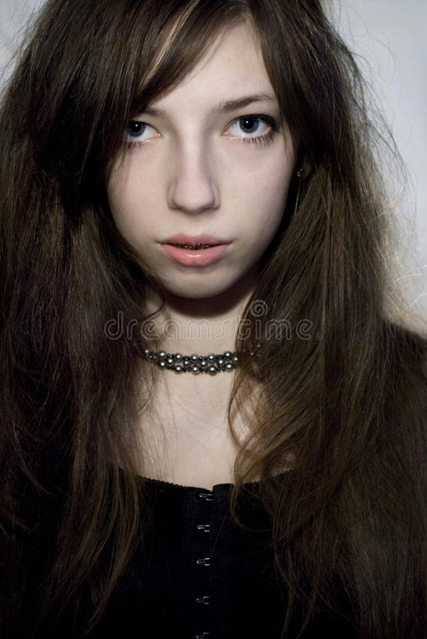 Attractive gothic woman. Portrait of attractive young gothic woman with chain around neck; studio background stock photos