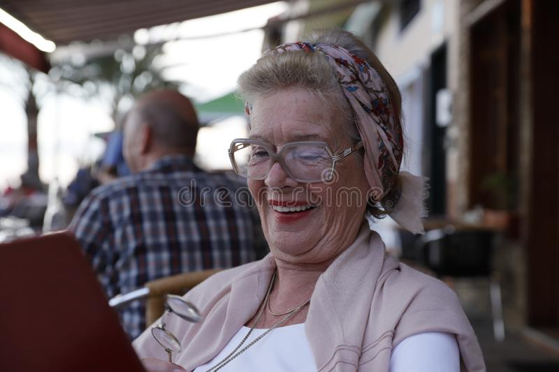 Attractive grandma in a restaurant. royalty free stock photography
