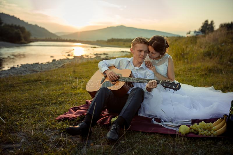 Attractive groom plays the guitar and his charming bride enjoys it during their picnic on the river bank during the stock photo