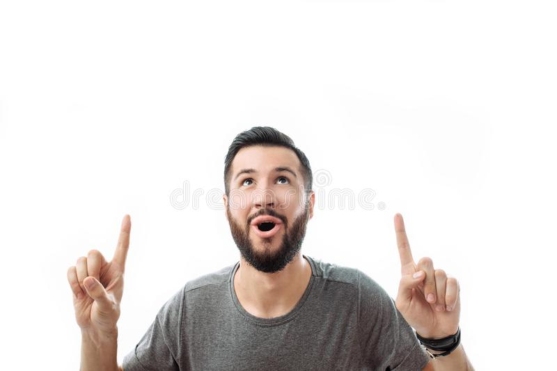 An attractive guy with a beard, with admiration and surprise poi. An attractive guy with a beard and a gray t-shirt, with admiration and surprise points his stock photography