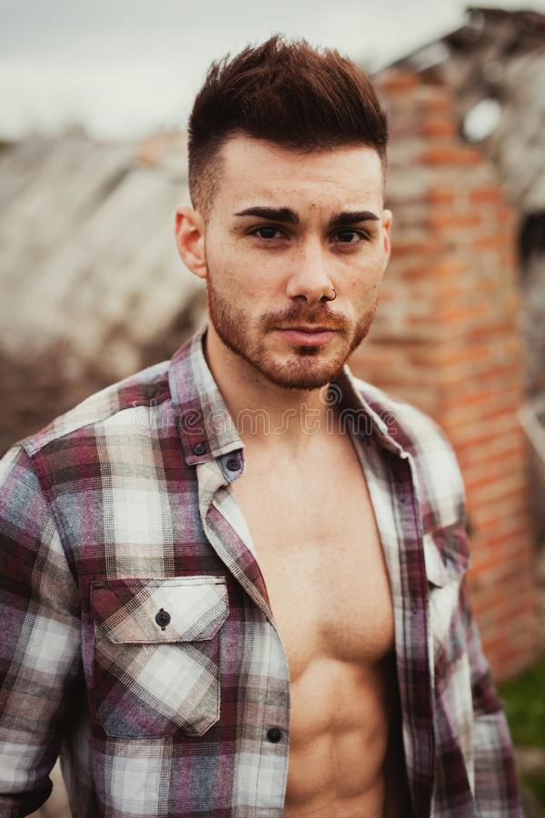 Attractive guy. Showing his strong chest and abs with the plaid shirt open royalty free stock image