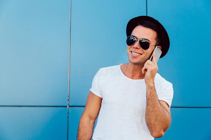 Attractive guy talking by cell phone, outdoors royalty free stock photo