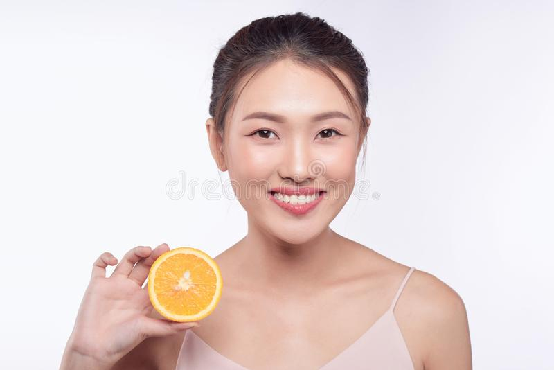 Attractive half-naked asian woman amiling while holding orange slices near her face.  royalty free stock images
