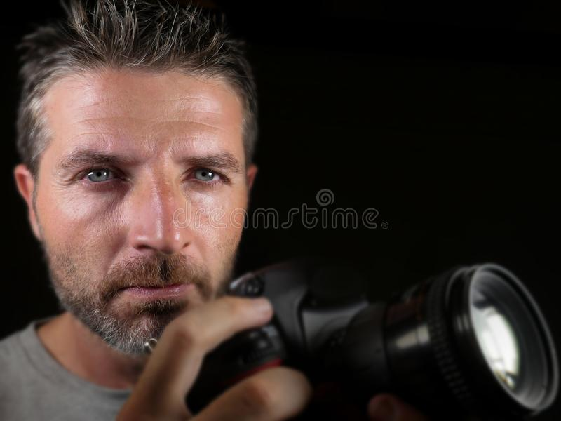 Attractive and handsome man on his 30d holding professional reflex photo camera next to his face isolated on black background in. Close up portrait of attractive stock photo