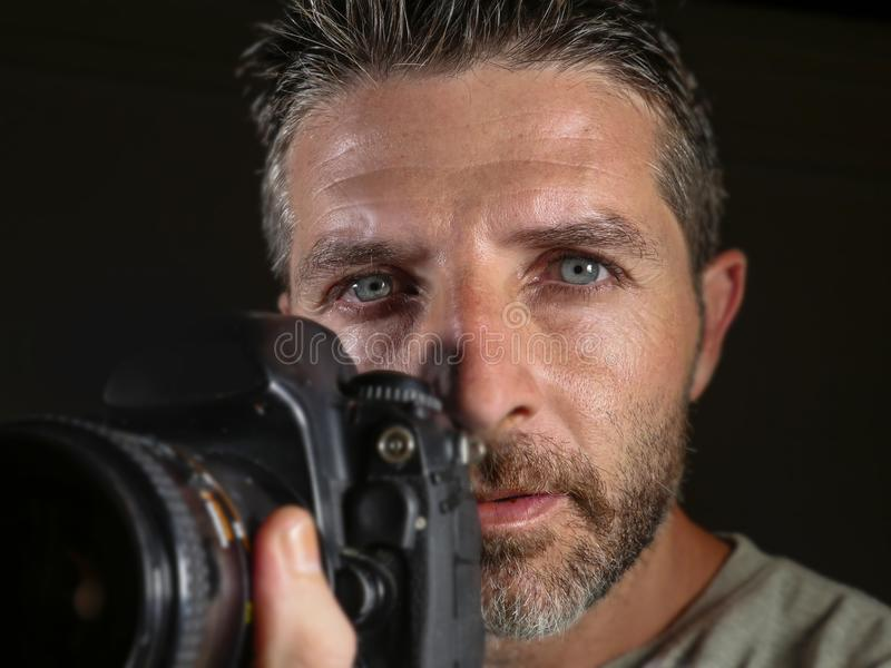 Attractive and handsome man on his 30d holding professional reflex photo camera next to his face isolated on black background in. Close up portrait of attractive royalty free stock photography