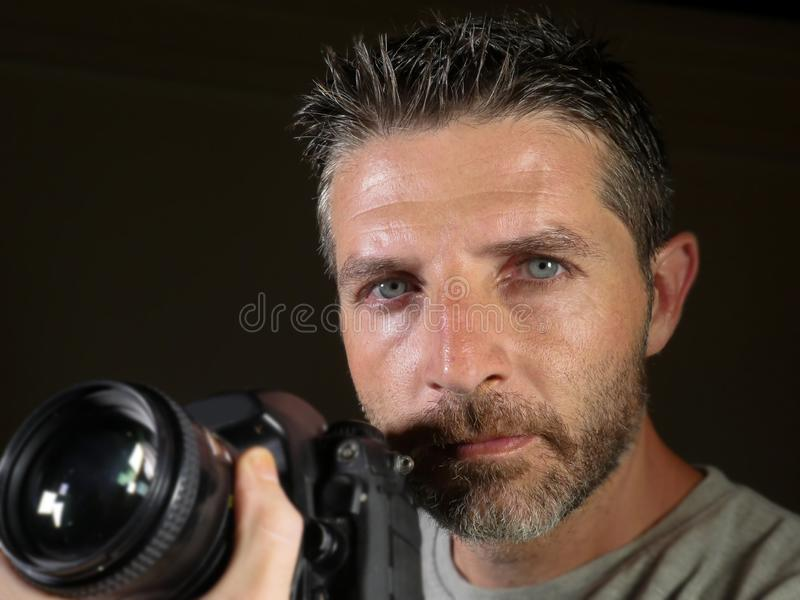 Attractive and handsome man on his 30d holding professional reflex photo camera next to his face isolated on black background in. Close up portrait of attractive stock image