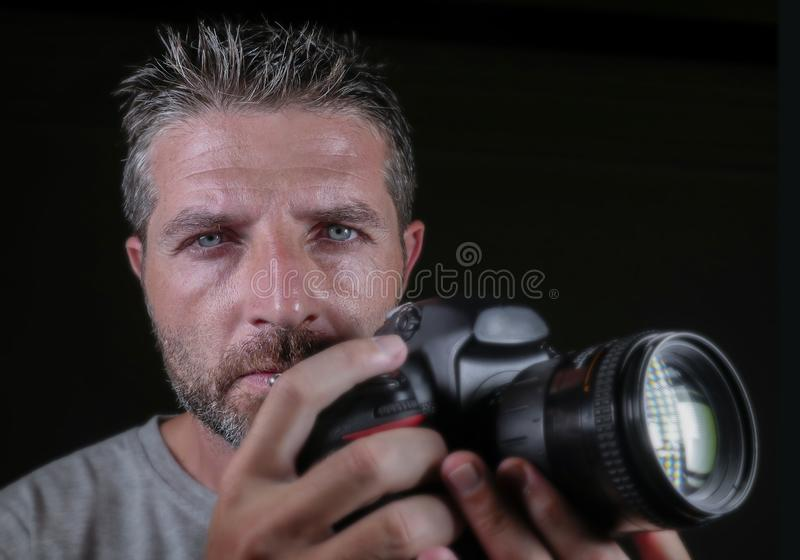 Attractive and handsome man on his 30d holding professional reflex photo camera next to his face isolated on black background in. Close up portrait of attractive stock photography