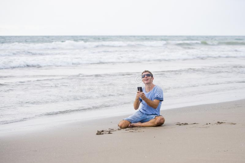 Attractive and handsome man on his 30s sitting on the sand relaxed on the beach laughing in front of the sea texting on mobile pho. Young attractive and handsome stock photo