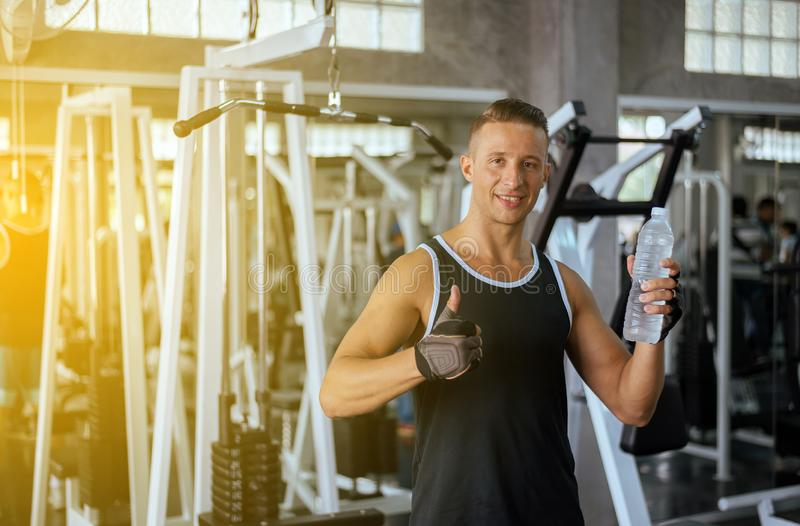 Attractive handsome man showing thumb up and drinking water in gym,Male break and relax after workout royalty free stock images