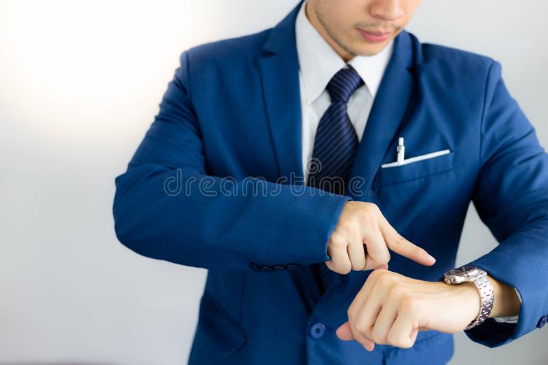 Attractive handsome young businessman is looking the time on wristwatch. Handsome guy is pointing finger to watch. He has stock photos