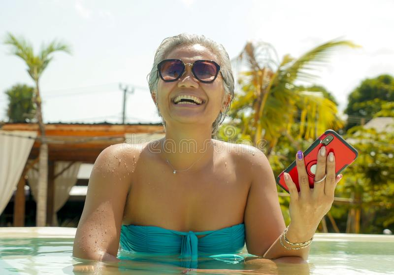 Attractive and happy Asian Indonesian middle aged 40s or 50s woman in bikini at tropical resort swimming pool using social media stock photography