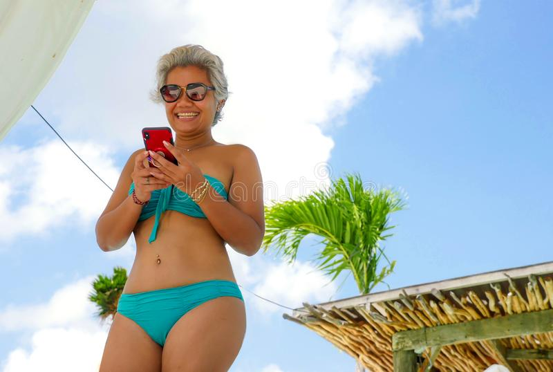 Attractive and happy Asian Indonesian middle aged 40s or 50s woman in bikini at tropical resort swimming pool using social media. App on mobile phone smiling stock photography